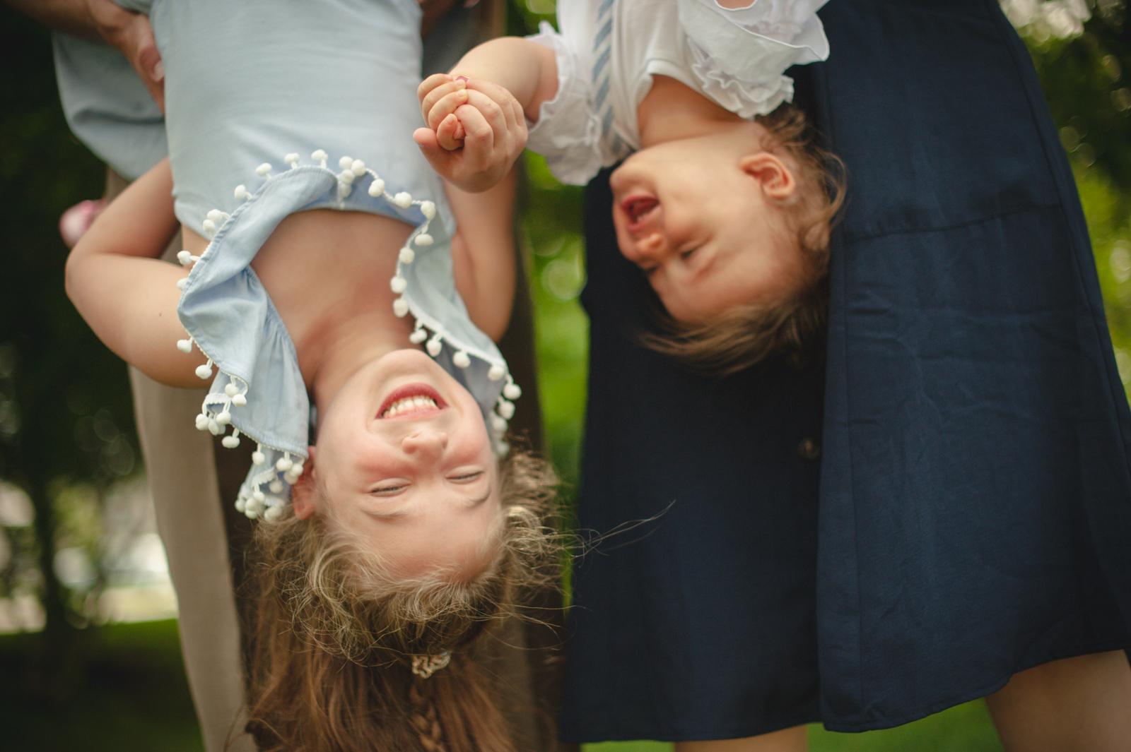 Sisters hanging upside down giggle.
