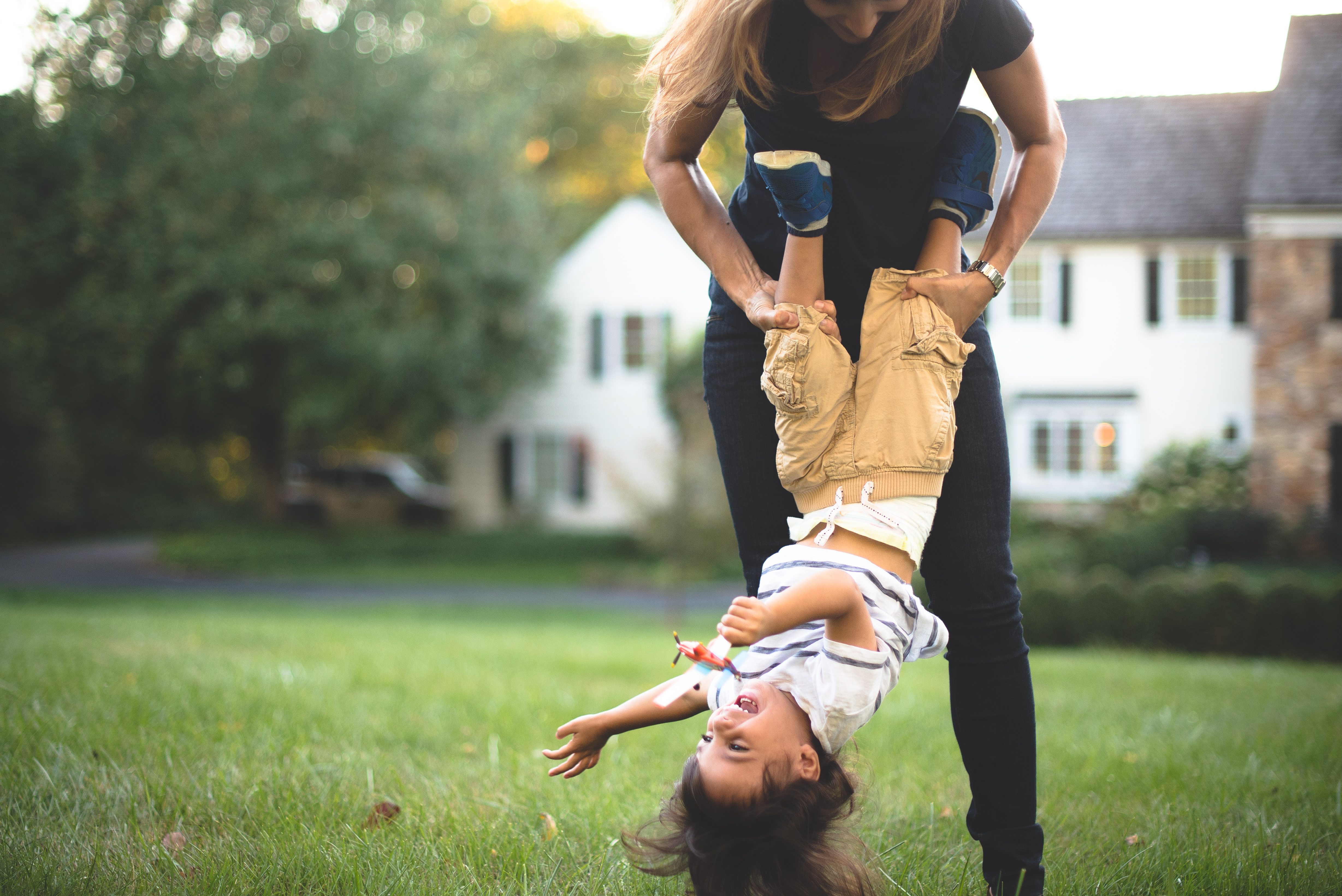 Little boy being swung upside down by mom in front yard.