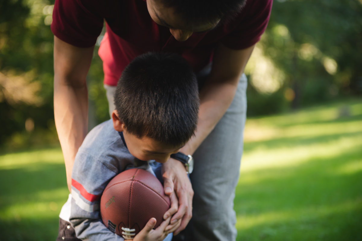 father and young son playing football